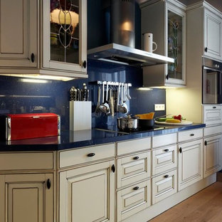 Zweizeilige, Mittelgroße Moderne Wohnküche ohne Insel mit Waschbecken, beigen Schränken, Kassettenfronten, Quarzwerkstein-Arbeitsplatte, Küchenrückwand in Blau, Rückwand aus Stein, Küchengeräten aus Edelstahl, gebeiztem Holzboden und grauem Boden in Sonstige