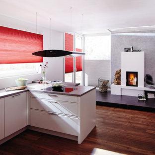 Mittelgroße Moderne Wohnküche in L-Form mit integriertem Waschbecken, flächenbündigen Schrankfronten, weißen Schränken, Laminat-Arbeitsplatte, Küchenrückwand in Weiß, Glasrückwand, Küchengeräten aus Edelstahl, dunklem Holzboden, Halbinsel, braunem Boden und grauer Arbeitsplatte in München