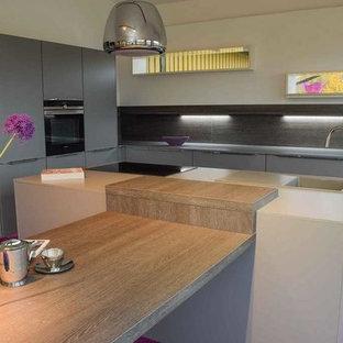 Inredning av ett modernt stort kök, med en nedsänkt diskho, släta luckor, grå skåp, bänkskiva i kvarts, grått stänkskydd, svarta vitvaror, heltäckningsmatta och en köksö