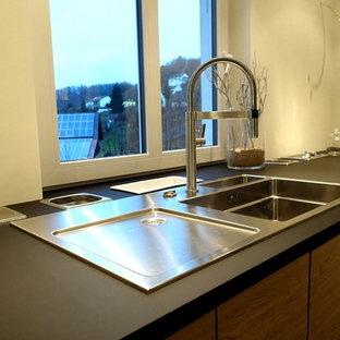 Geschlossene, Einzeilige, Mittelgroße Moderne Küche mit Einbauwaschbecken, flächenbündigen Schrankfronten, hellbraunen Holzschränken, Küchengeräten aus Edelstahl und schwarzem Boden in Sonstige