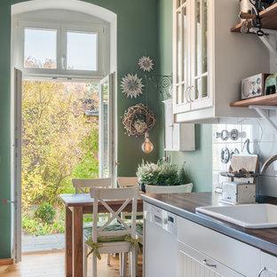 Kleine Nordische Küche mit brauner Arbeitsplatte, Einbauwaschbecken, flächenbündigen Schrankfronten, weißen Schränken, Arbeitsplatte aus Holz, braunem Holzboden und braunem Boden in Berlin