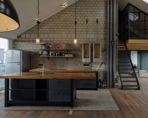 Offene, Zweizeilige Industrial Küche Mit Einbauwaschbecken, Schwarzen  Schränken, Arbeitsplatte Aus Holz, Küchenrückwand