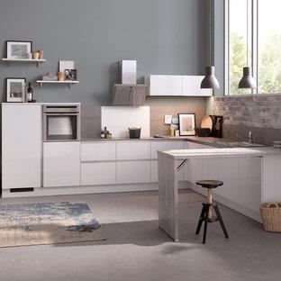 ライプツィヒの大きいコンテンポラリースタイルのおしゃれなキッチン (白いキャビネット、シルバーの調理設備の、リノリウムの床、ドロップインシンク、フラットパネル扉のキャビネット、木材カウンター、マルチカラーのキッチンパネル、レンガのキッチンパネル、グレーの床) の写真