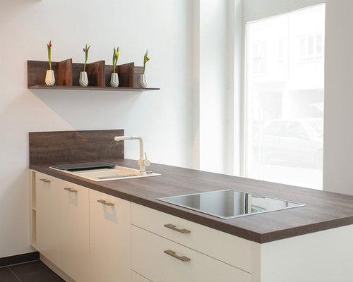 Moderne Küche Mit Einbauwaschbecken, Flächenbündigen Schrankfronten, Weißen  Schränken, Arbeitsplatte Aus Holz Und Halbinsel