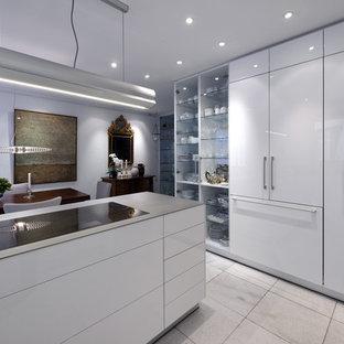 Moderne Küche mit flächenbündigen Schrankfronten, weißen Schränken und Kücheninsel in Bremen