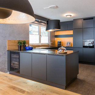 Design ideas for a mid-sized contemporary u-shaped eat-in kitchen in Nuremberg with black cabinets, granite benchtops, a peninsula, an integrated sink, flat-panel cabinets, brown splashback, timber splashback, black appliances and brown floor.