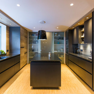 Design ideas for a mid-sized contemporary u-shaped separate kitchen in Nuremberg with an integrated sink, flat-panel cabinets, black cabinets, beige splashback, timber splashback, stainless steel appliances, bamboo floors, with island, beige floor and black benchtop.