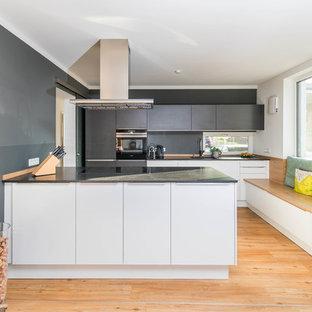 Zweizeilige, Mittelgroße Moderne Wohnküche mit weißen Schränken, Granit-Arbeitsplatte, flächenbündigen Schrankfronten, Küchenrückwand in Schwarz, Elektrogeräten mit Frontblende, hellem Holzboden, Halbinsel, beigem Boden und schwarzer Arbeitsplatte in Nürnberg
