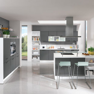 Large contemporary u-shaped open plan kitchen in Hamburg with an integrated sink, flat-panel cabinets, beige cabinets, wood benchtops, beige splashback, glass sheet splashback, stainless steel appliances, cement tiles, a peninsula and grey floor.