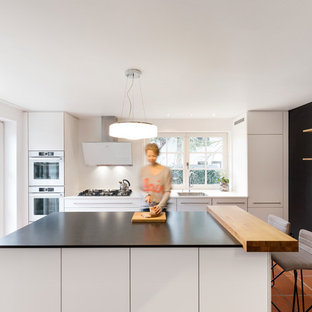 This is an example of a medium sized modern galley open plan kitchen in Stuttgart with a single-bowl sink, flat-panel cabinets, white cabinets, granite worktops, white splashback, wood splashback, white appliances, an island, black worktops and red floors.