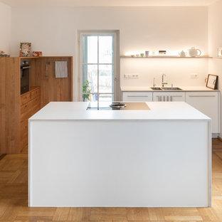Große, Offene Moderne Küche in L-Form mit flächenbündigen Schrankfronten, Laminat-Arbeitsplatte, Küchenrückwand in Weiß, Küchengeräten aus Edelstahl, weißer Arbeitsplatte, Unterbauwaschbecken, weißen Schränken, braunem Holzboden, Kücheninsel und braunem Boden in Stuttgart