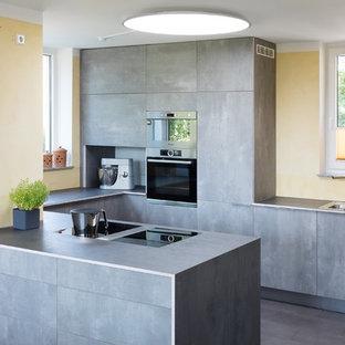 Aménagement d'une cuisine ouverte contemporaine en U de taille moyenne avec un évier 2 bacs, des portes de placard grises, un plan de travail en stratifié, une péninsule, un plan de travail gris, un placard à porte plane, un électroménager noir, un sol gris et une crédence jaune.
