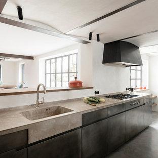 Idéer för att renovera ett avskilt, mellanstort industriellt grå grått kök, med en integrerad diskho, släta luckor, svarta skåp, bänkskiva i betong, svarta vitvaror, betonggolv och grått golv