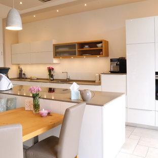 Mittelgroße, Zweizeilige Moderne Wohnküche mit Unterbauwaschbecken, flächenbündigen Schrankfronten, weißen Schränken, Küchenrückwand in Weiß, Elektrogeräten mit Frontblende, Kücheninsel, weißem Boden und grauer Arbeitsplatte in Bremen