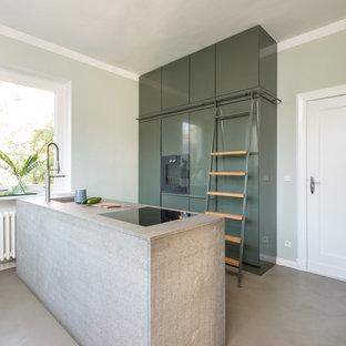 Zweizeilige, Mittelgroße Moderne Küche mit flächenbündigen Schrankfronten, grünen Schränken, grauer Arbeitsplatte, Unterbauwaschbecken, Elektrogeräten mit Frontblende, Halbinsel und grauem Boden in Berlin