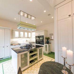 他の地域の中サイズのカントリー風おしゃれなキッチン (エプロンフロントシンク、シェーカースタイル扉のキャビネット、白いキャビネット、御影石カウンター、白いキッチンパネル、黒い調理設備、緑の床、黒いキッチンカウンター) の写真