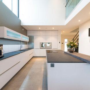 Diseño de cocina de galera, minimalista, extra grande, abierta, con fregadero de doble seno, armarios con paneles lisos, puertas de armario blancas, encimera de acrílico, salpicadero blanco, salpicadero de vidrio templado, electrodomésticos blancos, suelo de terrazo, una isla y suelo gris