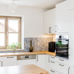 Mittelgroße Moderne Küche in L-Form mit Unterbauwaschbecken, Schrankfronten mit vertiefter Füllung, weißen Schränken, Arbeitsplatte aus Holz, bunter Rückwand, Elektrogeräten mit Frontblende, Kücheninsel und beiger Arbeitsplatte in München