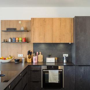 Kleine Moderne Küche in L-Form mit flächenbündigen Schrankfronten, grauen Schränken, Küchenrückwand in Schwarz, Elektrogeräten mit Frontblende, Halbinsel und schwarzer Arbeitsplatte in Köln