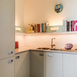 Mid-Century Küche mit Doppelwaschbecken, flächenbündigen Schrankfronten, türkisfarbenen Schränken, Laminat-Arbeitsplatte, Küchenrückwand in Weiß, Rückwand aus Metrofliesen, schwarzen Elektrogeräten, Linoleum, türkisem Boden und grauer Arbeitsplatte in Brisbane