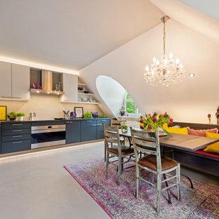 Große Moderne Wohnküche ohne Insel in L-Form mit flächenbündigen Schrankfronten, Mineralwerkstoff-Arbeitsplatte, Küchenrückwand in Beige, schwarzer Arbeitsplatte, grauen Schränken, Betonboden, grauem Boden und gewölbter Decke in München
