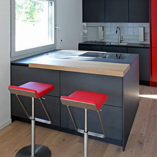 Zweizeilige Moderne Küche mit Waschbecken, flächenbündigen Schrankfronten, schwarzen Schränken, Küchenrückwand in Grau, Glasrückwand, hellem Holzboden, Halbinsel, beigem Boden und schwarzer Arbeitsplatte in Frankfurt am Main
