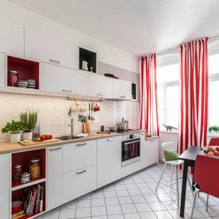 Einzeilige Moderne Küche mit weißen Schränken und Arbeitsplatte aus Holz in Hamburg