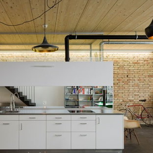 Design ideas for a medium sized industrial single-wall open plan kitchen in Frankfurt with concrete flooring, an integrated sink, flat-panel cabinets, white cabinets, stainless steel worktops, white splashback, mirror splashback, black appliances and no island.