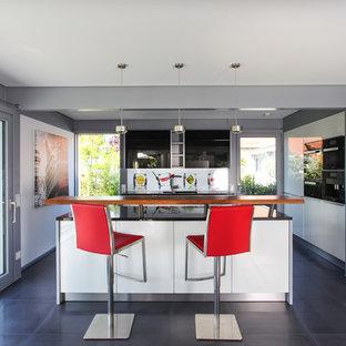 Offene, Mittelgroße Moderne Küche in L-Form mit Einbauwaschbecken, flächenbündigen Schrankfronten, weißen Schränken, Küchenrückwand in Weiß, schwarzen Elektrogeräten, Zementfliesen, Halbinsel und schwarzem Boden in Sonstige
