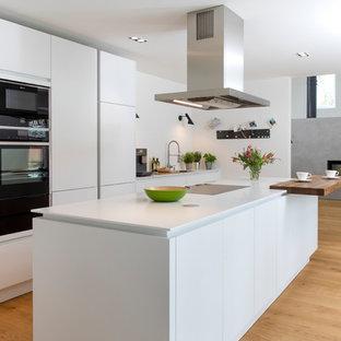 Offene, Große, Zweizeilige Moderne Küche mit flächenbündigen Schrankfronten, weißen Schränken, Mineralwerkstoff-Arbeitsplatte, Küchenrückwand in Weiß, schwarzen Elektrogeräten, hellem Holzboden, Kücheninsel, weißer Arbeitsplatte und beigem Boden in Hamburg
