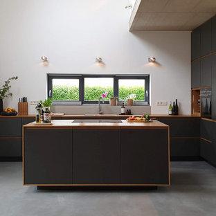 Offene Nordische Küche mit Einbauwaschbecken, flächenbündigen Schrankfronten, schwarzen Schränken, Arbeitsplatte aus Holz, Betonboden, Kücheninsel und grauem Boden in Köln