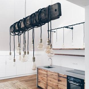 ベルリンの中サイズのコンテンポラリースタイルのおしゃれなキッチン (一体型シンク、フラットパネル扉のキャビネット、中間色木目調キャビネット、コンクリートカウンター、白いキッチンパネル、黒い調理設備、無垢フローリング) の写真