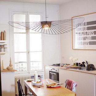 ベルリンの大きいエクレクティックスタイルのおしゃれなキッチン (ドロップインシンク、フラットパネル扉のキャビネット、白いキャビネット、木材カウンター、白いキッチンパネル、セメントタイルのキッチンパネル、シルバーの調理設備、無垢フローリング、アイランドなし、グレーの床) の写真