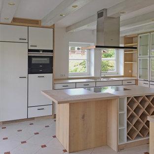Lantlig inredning av ett avskilt, stort beige beige l-kök, med en dubbel diskho, luckor med profilerade fronter, vita skåp, bänkskiva i kvartsit, vitt stänkskydd, svarta vitvaror, målat trägolv och beiget golv
