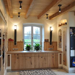 ドルトムントの巨大なカントリー風おしゃれなダイニングキッチン (中間色木目調キャビネット、ステンレスカウンター、シルバーの調理設備の、フラットパネル扉のキャビネット、ダブルシンク、アイランドなし、木材のキッチンパネル) の写真