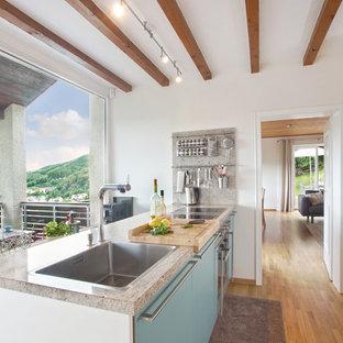 Zweizeilige, Mittelgroße Moderne Küche mit Einbauwaschbecken, flächenbündigen Schrankfronten, türkisfarbenen Schränken, Granit-Arbeitsplatte, Küchengeräten aus Edelstahl, Kücheninsel, braunem Holzboden und braunem Boden in Sonstige