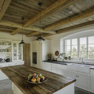 Geschlossene Country Küche in L-Form mit Landhausspüle, Schrankfronten im Shaker-Stil, weißen Schränken, Küchenrückwand in Weiß, schwarzen Elektrogeräten, Kücheninsel und Granit-Arbeitsplatte in Essen