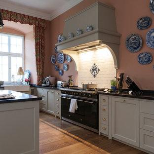 Offene, Große Country Küche in L-Form mit Landhausspüle, Kassettenfronten, Granit-Arbeitsplatte, Küchenrückwand in Rosa, Rückwand aus Keramikfliesen, bunten Elektrogeräten, braunem Holzboden und Kücheninsel in Köln