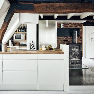 Offene, Kleine Landhaus Küche mit flächenbündigen Schrankfronten, weißen Schränken, Arbeitsplatte aus Holz und Halbinsel in Hamburg