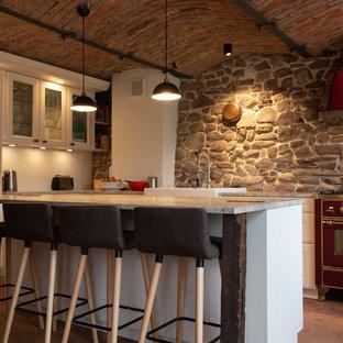 フランクフルトの地中海スタイルのおしゃれなアイランドキッチン (落し込みパネル扉のキャビネット、白いキャビネット、グレーのキッチンパネル、カラー調理設備、レンガの床、赤い床、グレーのキッチンカウンター) の写真