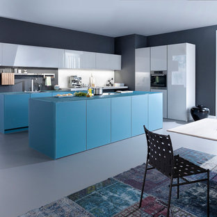Large contemporary eat-in kitchen photos - Large trendy l-shaped eat-in kitchen photo in Stuttgart with flat-panel cabinets, blue cabinets, a single-bowl sink, paneled appliances and an island