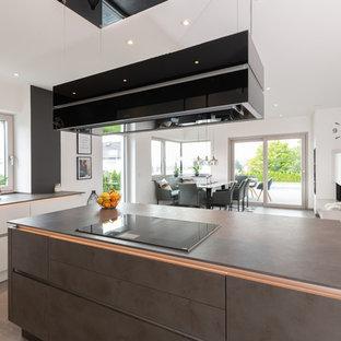 Große Moderne Wohnküche in L-Form mit flächenbündigen Schrankfronten, grauen Schränken, Mineralwerkstoff-Arbeitsplatte, Küchenrückwand in Weiß, Küchengeräten aus Edelstahl, Terrakottaboden, Kücheninsel, grauem Boden und grauer Arbeitsplatte in Nürnberg