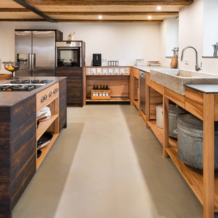 Large rustic open concept kitchen ideas - Large mountain style l-shaped vinyl floor and beige floor open concept kitchen photo in Stuttgart with an integrated sink, open cabinets, medium tone wood cabinets, black appliances and two islands