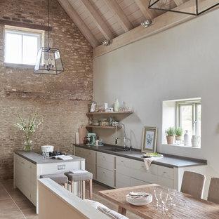 Modelo de cocina lineal, contemporánea, extra grande, abierta, con armarios con paneles lisos, puertas de armario blancas, una isla y fregadero integrado