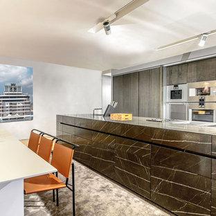 Imagen de cocina contemporánea, grande, abierta, con fregadero de un seno, armarios con paneles lisos, puertas de armario negras y una isla