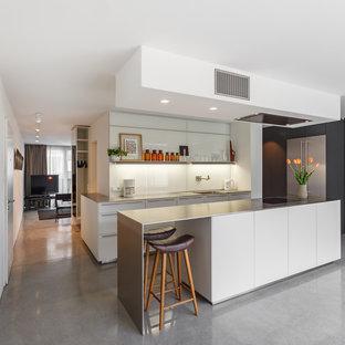 Offene, Einzeilige, Mittelgroße Moderne Küche mit flächenbündigen Schrankfronten, weißen Schränken, Edelstahl-Arbeitsplatte, Küchenrückwand in Weiß, Glasrückwand, Betonboden, Kücheninsel, grauem Boden und integriertem Waschbecken in Hamburg