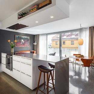 Offene, Mittelgroße Moderne Küche mit flächenbündigen Schrankfronten, weißen Schränken, Kücheninsel, grauem Boden und grauer Arbeitsplatte in Hamburg