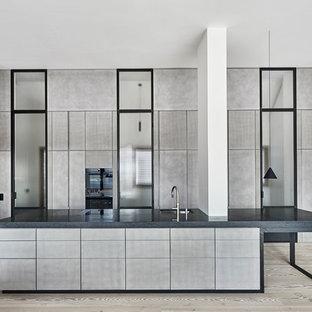 Moderne Küche mit Unterbauwaschbecken, flächenbündigen Schrankfronten, grauen Schränken, schwarzen Elektrogeräten, hellem Holzboden, Kücheninsel, beigem Boden und schwarzer Arbeitsplatte in Köln