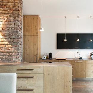 Свежая идея для дизайна: большая кухня-гостиная в современном стиле с монолитной раковиной, плоскими фасадами, фасадами цвета дерева среднего тона, столешницей из нержавеющей стали, островом и темным паркетным полом - отличное фото интерьера