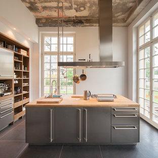 Ejemplo de cocina urbana, grande, cerrada, con armarios abiertos, puertas de armario en acero inoxidable, encimera de madera, electrodomésticos de acero inoxidable, una isla y fregadero encastrado